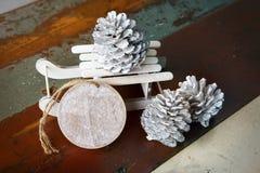 Träetikett med leksakjulsläden och pinecones arkivfoton