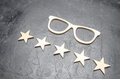Träexponeringsglas och fem stjärnor på en konkret bakgrund Högkvalitativa exponeringsglas Den bästa optiken Korrigering av vision royaltyfria bilder