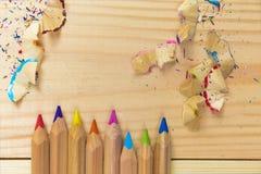 Träfärgrika blyertspennor med att vässa shavings, på trätabellen Arkivbild