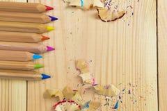 Träfärgrika blyertspennor med att vässa shavings, på trätabellen Royaltyfri Fotografi