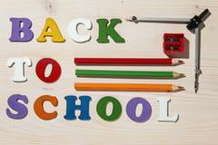 Träfärgrika bokstäver som tillbaka stavar till skolan med skolan Offi Royaltyfria Foton