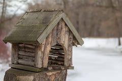 Träfågelförlagematare i form av ett landshus arkivbilder