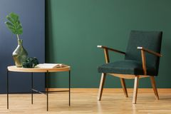 Träfåtölj bredvid tabellen och boken i grön och blå vardagsruminre Verkligt foto arkivbild