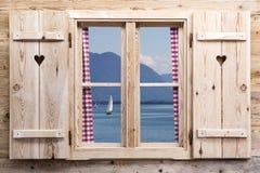Träfönster med en sjö som reflexioner Arkivbilder