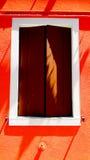 Träfönster på den orange färgväggen royaltyfria foton