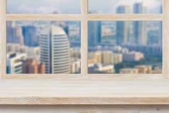 Träfönsterbräda över suddigt fönster för stadssiktsho Royaltyfria Bilder