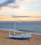 Träfartyg på en strand på solnedgången Royaltyfri Foto