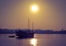 Träfartyg på floden i soluppgången Arkivfoto