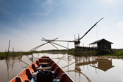 Träfartyg som kryssar omkring längs sjön som passerar fiskarens hus Royaltyfri Foto