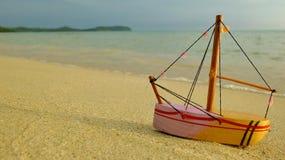 Träfartygleksak på stranden arkivbilder