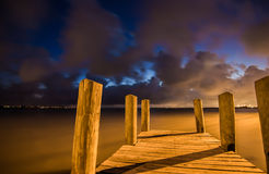 Träfartygskeppsdocka på solnedgången med härliga moln Royaltyfri Bild