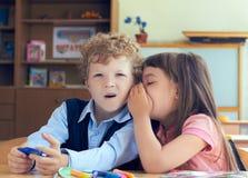 Träffande hemlighet för flicka till den förvånade lockiga pojken i klassrum Royaltyfri Fotografi