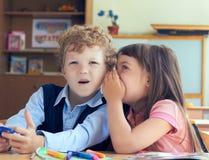 Träffande hemlighet för liten flicka till den förvånade pojken i klassrum Arkivfoto