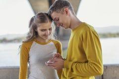 Träffas par av tonåringar på invallningen av floden Arkivbild