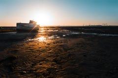 Träfiskebåt på stranden på solnedgången Arkivfoto