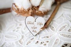 Träformad hjärta med skriftliga ord tro, hopp, förälskelse på den, tappningstilsort royaltyfri foto
