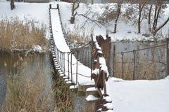 Träfot- upphängningbro över floden royaltyfria foton