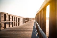 Träfotbro i stranden Arkivfoto