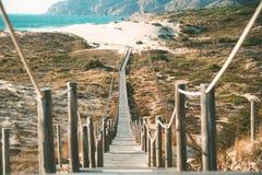 Träfotbro i stranden Arkivfoton