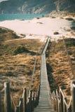 Träfotbro vid stranden Fotografering för Bildbyråer