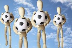 Träfyra figurerar med fotboll klumpa ihop sig Arkivfoton