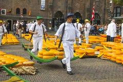 Träger, die mit Käsen im Markt des holländischen Käses gehen Stockbild