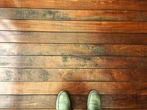 Trägolv med mina egna skor på trägångbanan arkivbild
