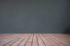 Trägolv- och grå färgväggbakgrund Arkivbilder