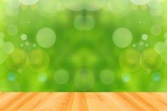Trägolv och grön bokehbakgrund för abstrakt begrepp Arkivbild