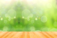 Trägolv och grön bokehbakgrund för abstrakt begrepp Arkivfoto