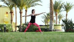 Trägt das Mädchen zur Schau, das grundlegende Übungen vom Yoga tut, das barfuß auf dem Rasen steht Brunette in der stilvollen Spo stock footage