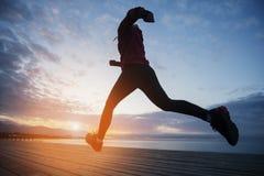 Trägt die Frau zur Schau, die auf hölzerner Promenade läuft Sonnenaufgangküste Lizenzfreies Stockfoto