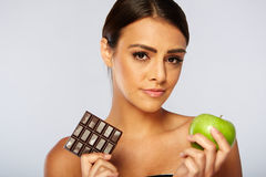 Trägt die Frau zur Schau, die Wahl zwischen gesundem Apfel trifft Lizenzfreie Stockfotos