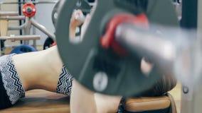 Trägt die junge Frau zur Schau, die an Übungen mit Barbell tut stock video footage
