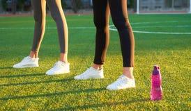 Trägt Flasche Wasser und Athlet ` s Füße auf den warmen Strahlen des Rasens morgens des Lichtes zur Schau Sport, Eignung, Gesundh Lizenzfreie Stockfotografie