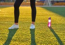 Trägt Flasche Wasser und Athlet ` s Füße auf den warmen Strahlen des Rasens morgens des Lichtes zur Schau Sport, Eignung, Gesundh Stockbild