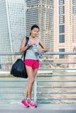 Trägt Wasserflasche zur Schau Athletische Frau in der Sportkleidung, die Flasche hält Stockbilder