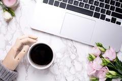 Trähanden, kaffe och rosa blommor marmorerar på kontorsbakgrund arkivbild