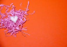 Trähjärta på den orange pappers- bakgrunden med rosa skivat papper Valentindagbakgrund med handgjorda leksakhjärtor royaltyfria bilder