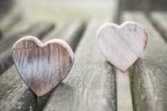 Trähjärtor på bänk i utomhus- - älska begreppet royaltyfria foton