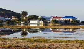 Trähus bredvid en sjö eller en lagun Fotografering för Bildbyråer