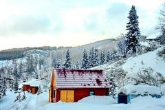 Trähus i bergen och runt om mycket snö arkivfoto