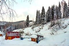 Trähus i bergen och runt om mycket snö royaltyfria foton