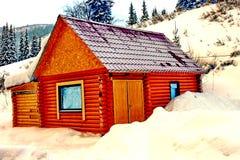 Trähus i bergen och runt om mycket snö arkivbild