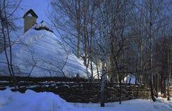 Trähus i en vinterskog under ett snölock arkivbilder
