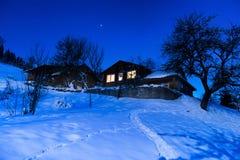 Trähus i snö på vinternatten arkivfoton