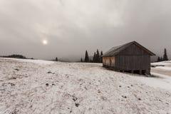 Trähus i vinterskog Fotografering för Bildbyråer
