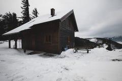 Trähus i vinterskog på ett berg royaltyfria bilder