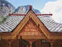 Trähus med dekorativ gravyr i berg Arkivfoto
