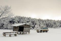 Trähus med en bil i en snöig skog royaltyfri fotografi